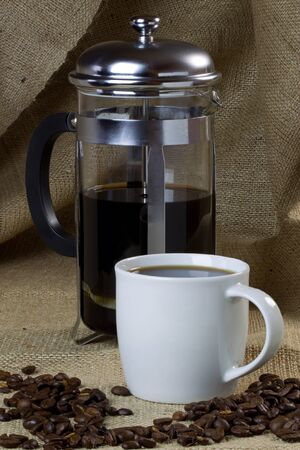 A mug of coffee on a hessian background with beans and a cafetiere photo