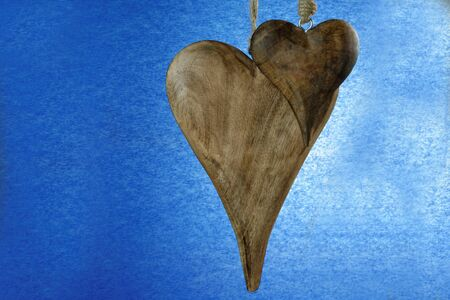 Two wooden hearts hanging against a blue background - love concept photo