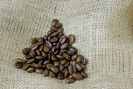 A close up of coffee beans on a hessian background with copy space photo