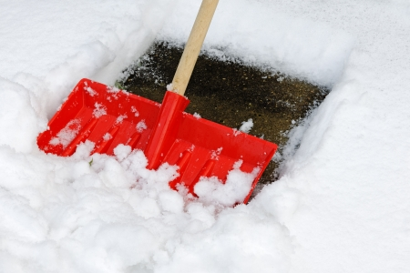 A snow shovel being used to clear a pavement - close up