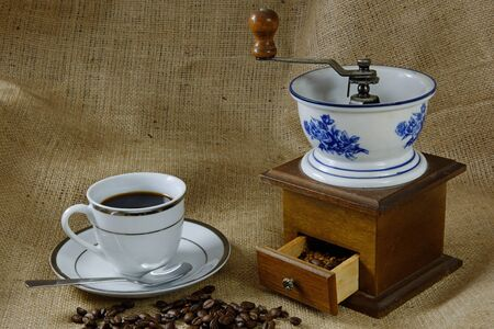 A cup of coffee on a hessian background with an antique coffee mill photo