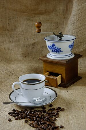 A cup of coffee on a hessian background with an antique coffee grinder photo