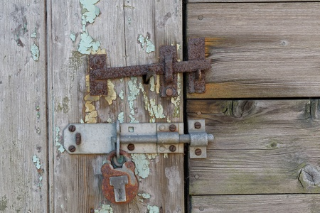 An old latch and padlock on a distressed door photo