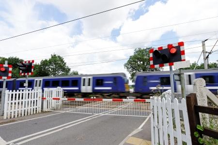 Passage à niveau avec le train de passagers à la vitesse et les barrières fermées Banque d'images - 21632857