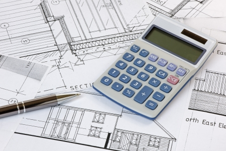 A calculator and pen on some house plans  Plans are copyright-free