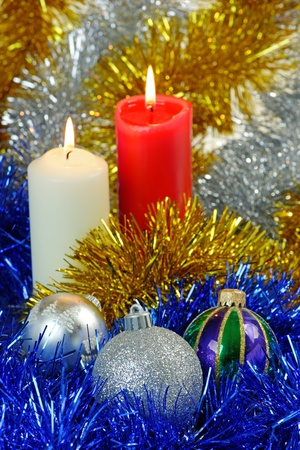 Christmas baubles and candles against a twinkling tinsel background photo