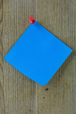 Blue post it note on a wooden background with red thumb-tack photo