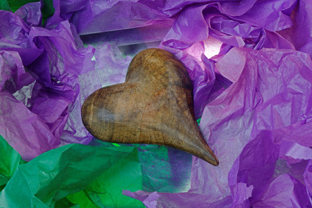 denoting: Antique wooden heart denoting love, in a gift box with coloured tissue paper. Stock Photo