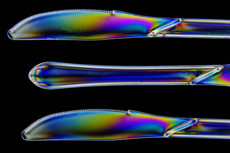 polarised: Plastic knives shot in double polarised lighting, in closeup Stock Photo