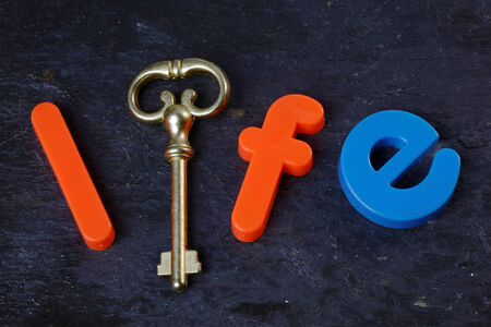 Antique key on a slate background with the word life in letters photo