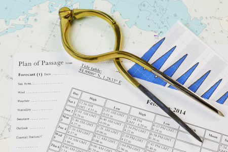 Navigation equipment and tide tables on a chart Stock Photo