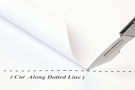 Close up of a scalpel cutting along a dotted line on a sheet of white paper. Stock Photo