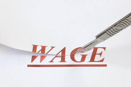 denoting: A scalpel cutting through the word Wage. Concept denoting a wage or salary cut, or reduced income because of a falling economy. Stock Photo