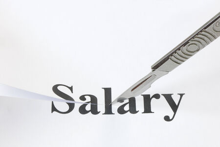 denoting: Scalpel cutting through the word Salary. Concept denoting a cut in income or salary caused by economic troubles and a lowering of standard of living.