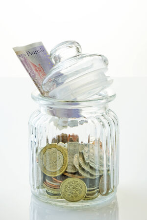 tax tips: Money, or savings in an old jar- with reflection. Financial concept. Stock Photo