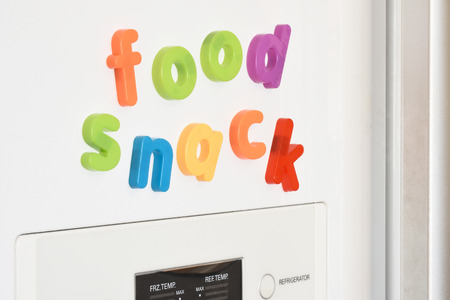 fridge: The words Food & Snack spelled out in fridge magnets on the door of a fridge. Stock Photo