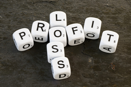 Letter dice on slate background  showing the words Profit and Loss. Business concept denoting success and failure photo