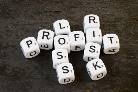 perdidas y ganancias: Dados de letras sobre fondo de pizarra que muestra las palabras de beneficio, riesgo y las p�rdidas. Concepto de negocio que denota el �xito y el fracaso