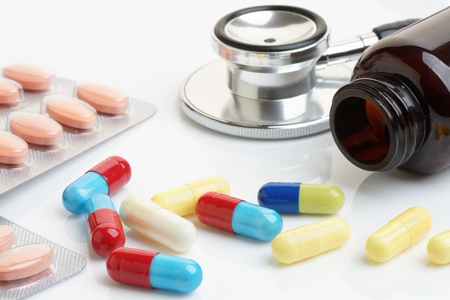 medicine bottle: Close up of statin and beta-blocker pills and capsules with bottle and stethoscope.