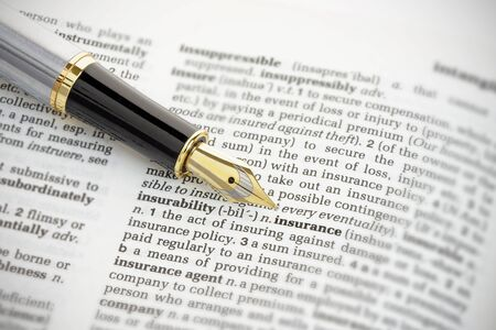 surety: Fountain pen pointing to the word insurance on the page of a generic dictionary.