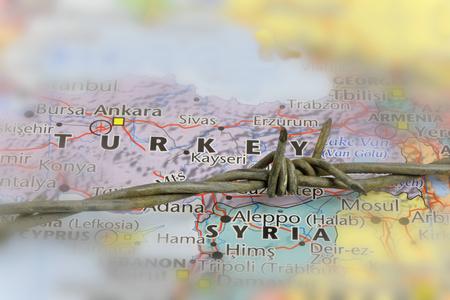 Een onderdeel van prikkeldraad na de grens tussen Turkije en Syrië op een kaart.  Border Defence concept.