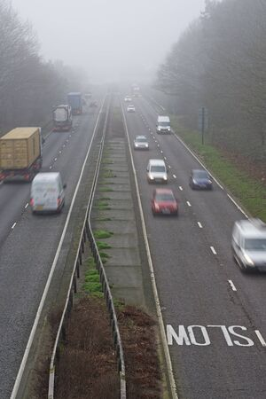 unreadable: Misty winter morning on a busy road in the UK. All logos blurred and unreadable.
