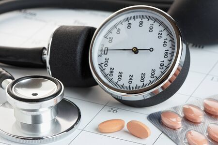Statins or generic medicines on a calendar with a sphygmanometer and stethoscope. Medical check up concept. Stock Photo