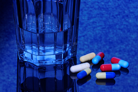 Capsules with a glass of water. Medical concept.