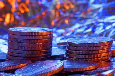heap up: Heap of silver coins close up in colored lighting. Shallow depth of field