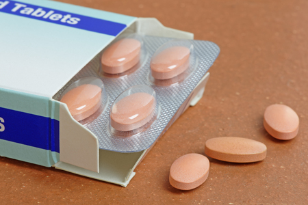 Statins, or generic pills, pouring from a pack.