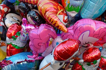 Helium filled carnival balloons in close up - a colorful background