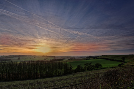 View across the hills and fields of the Lincolnshire Wolds,UK, with a winter sunset