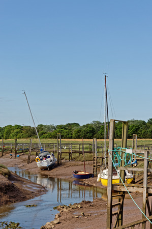 Yachts moored at low tide in Steeping River, Gibraltar Point,UK. A nature reserve on the edge of The Wash in Lincolnshire,UK Stock Photo