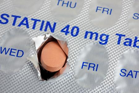 Una compressa di statine che emerge da un blister settimanale contrassegnato