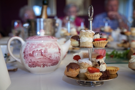 afternoon tea: Cake stand with mini cakes on a table set for an afternoon tea party