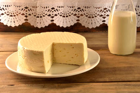 Sliced white cheese on the table with bottle of milk Stock fotó