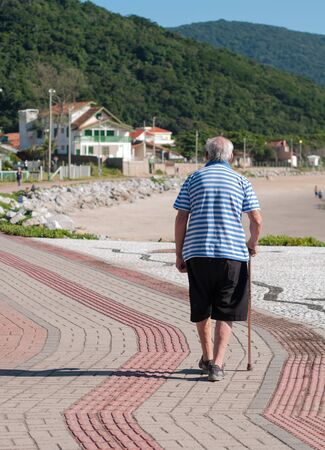 armacao: Elder walk on the sidewalk in the seaside Beach Armacao in FlorianopolisBrazil