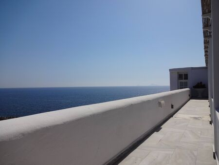 facing a wall: white wall facing the sea Stock Photo