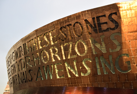 The sun setting on the Wales Millennium Centre - the text says  the text says Truth is as clear as glass forged in the flames of inspiration 스톡 콘텐츠