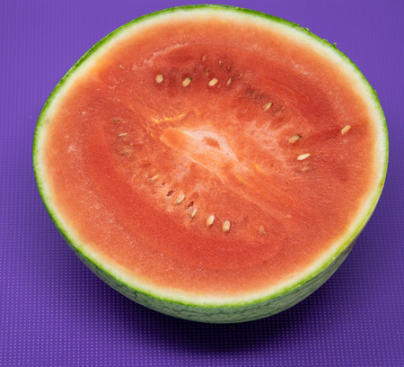 A water melon that has been sliced in half resting on a purple chopping board