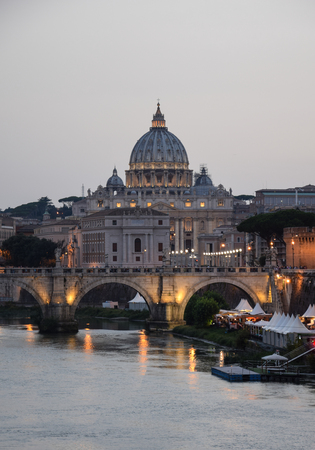 The dome of St Peters Basilica seen down the Tiber river at twilight Editorial