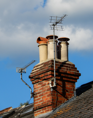 A Pair of Television aerials attached to a stack of four chimneys