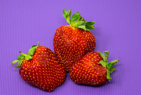Reading, United Kingdom - July 08 2018:   Three red strawberries on a purple chopping board