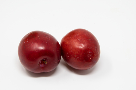 A photo of two plums on a white background