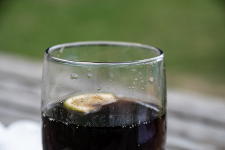 Reading, United Kingdom - August 19 2018:   A Pint glass of Cola with a slice of lemon in, in a pub garden