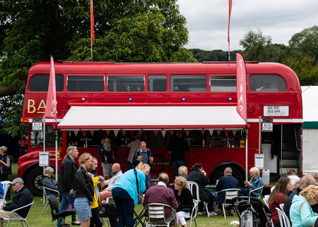 Henley-on-Thames, United Kingdom - August 27 2018:   A classic London Routemaster bus converted for use as a mobile bar, seen here at Henley Country Craft Show surrounded by customers having a drink