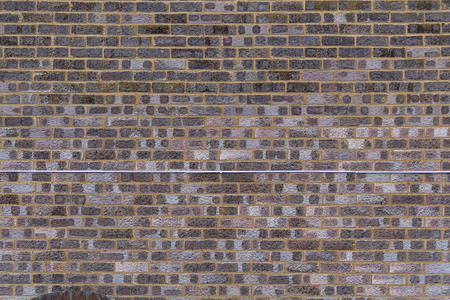 A Brick and mortar wall with a telephone wire running across it. Stok Fotoğraf