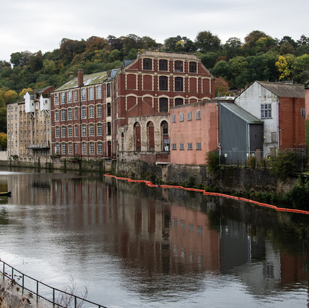 Old factories adn warehouses reflected in the water of the River Avon