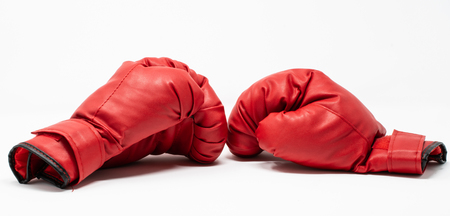 A pair of red boxing gloves used for training with a punch bag