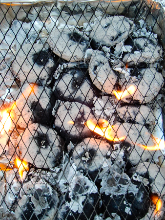 A top down view of a lit and burning disposable barbecue